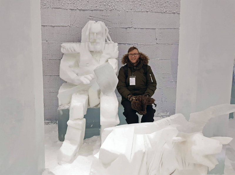 Markus sitting by an ice sculpture of Thor at Icehotel