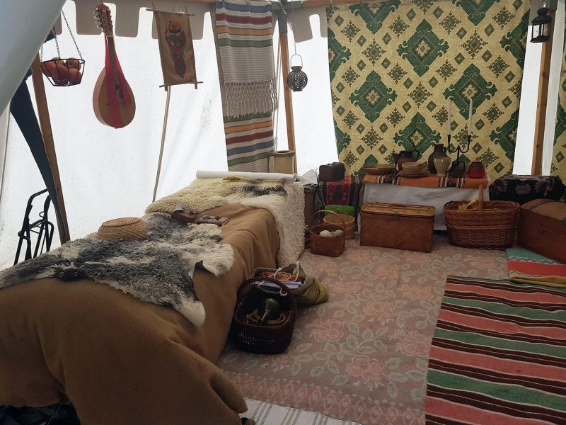 Inside a tent with medieval furniture and decorations